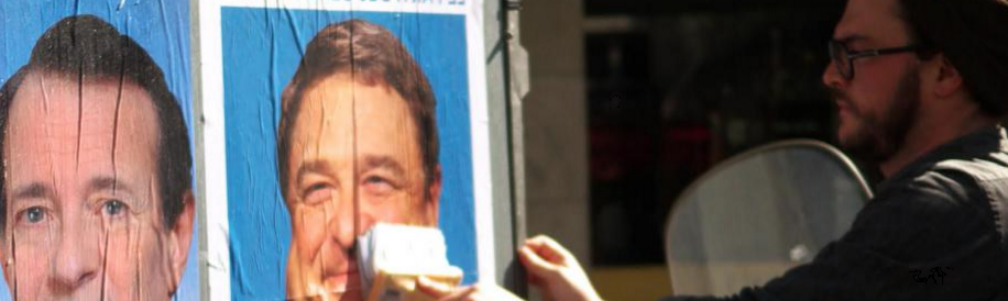 L'artiste colle ses parodies d'affiches électorales.