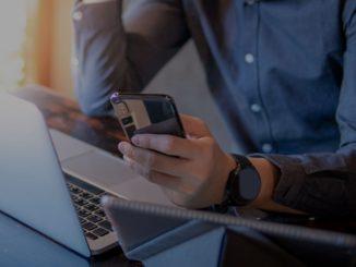 Homme avec un smartphone devant un ordinateur portable