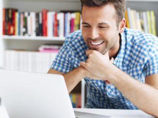 Homme qui sourit devant son ordinateur