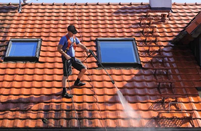 Homme nettoyant sa toiture