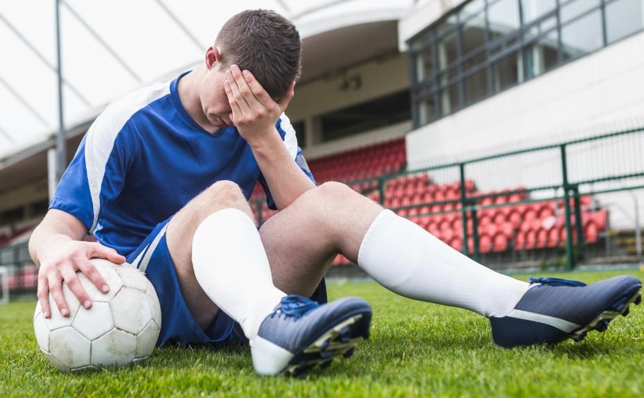 Un footballeur épuisé assis sur la pelouse