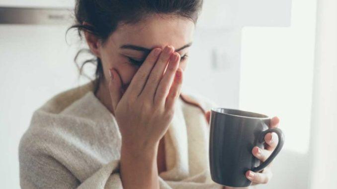 Une femme malade tenant un mug