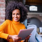 Une femme souriante avec un ipad dans les mains