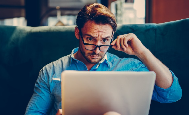Homme avec des lunettes devant son ordinateur