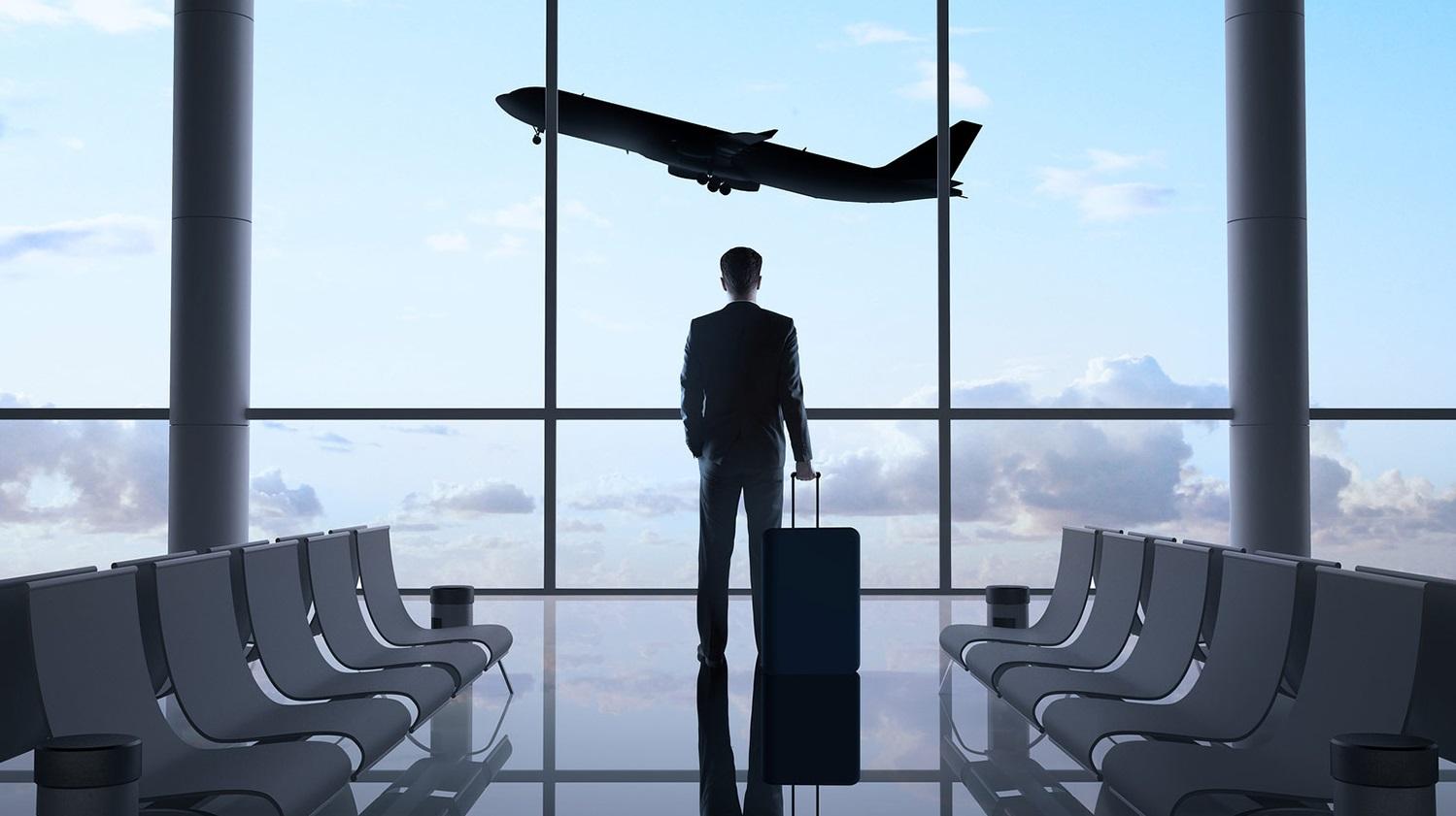 Homme avec une valise regardant un avion voler