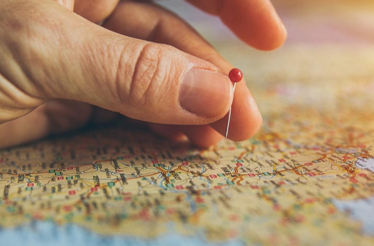 Carte avec une main et une punaise