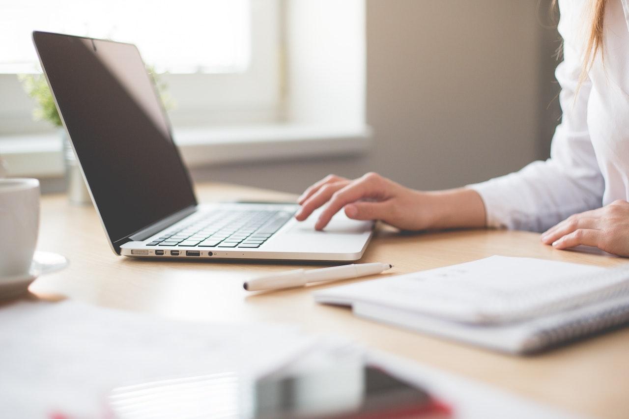 femme utilise ordinateur portable bureau cahier stylo suit formation